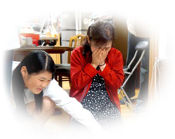 涙を浮かべるお母さんの写真